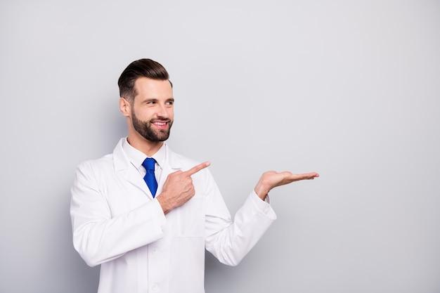 Portrait de son il nice attrayant heureux joyeux joyeux confiant doc tenant sur la paume montrant une nouvelle solution de nouveauté annonce annonce alternative isolée sur couleur pastel gris blanc clair