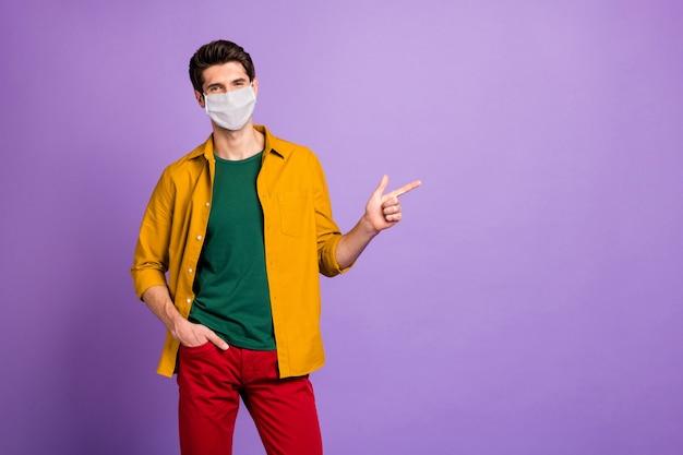 Portrait de son mec séduisant portant un masque de sécurité démontrant l'espace de copie mers cov grippe fièvre élevée décontamination thérapie traitement médecine aide isolé fond de couleur pastel violet lilas