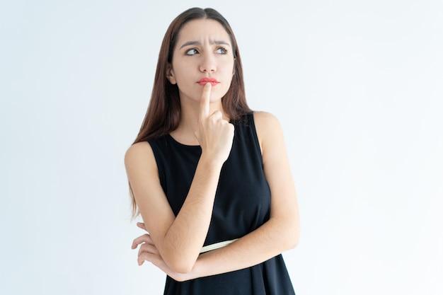 Portrait de songeuse jeune femme asiatique debout avec la main sur le menton