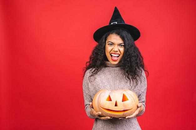 Portrait de sorcière afro-américaine halloween tenant la citrouille