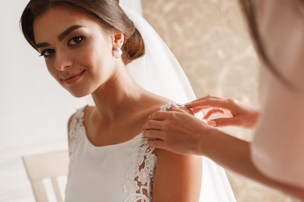 Portrait souriant belle mariée en robe chic et voile intérieur dans la chambre d'hôtel