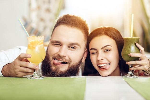 Portrait souriant couple amoureux buvant des cocktails