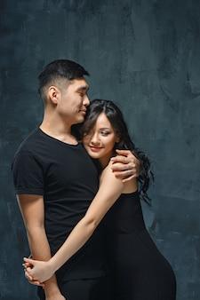 Portrait de souriant couple coréen sur un gris