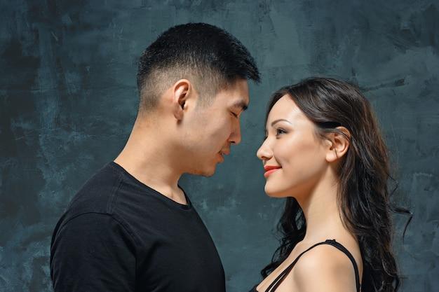 Portrait de souriant couple coréen sur un mur gris