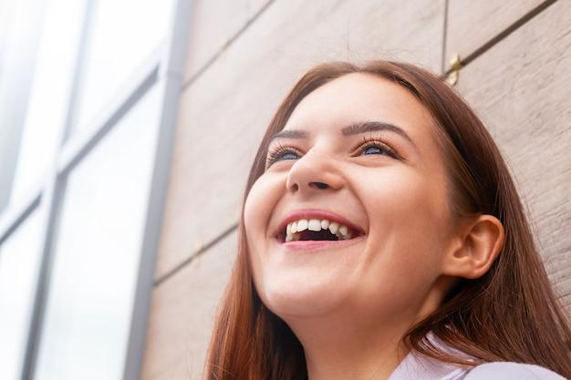 Portrait souriant d'étudiant de fille caucasienne se bouchent