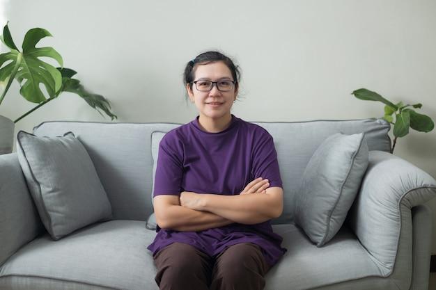 Portrait souriant d'une femme asiatique d'âge moyen assis sur le canapé dans la maison