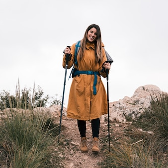 Portrait, de, a, souriant, femme, randonneur, tenue, bâton randonnée, regarder appareil-photo