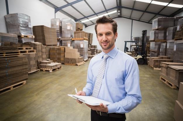 Portrait de souriant gestionnaire tenant le presse-papiers
