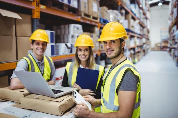 Portrait, de, souriant, gestionnaires entrepôt, portable