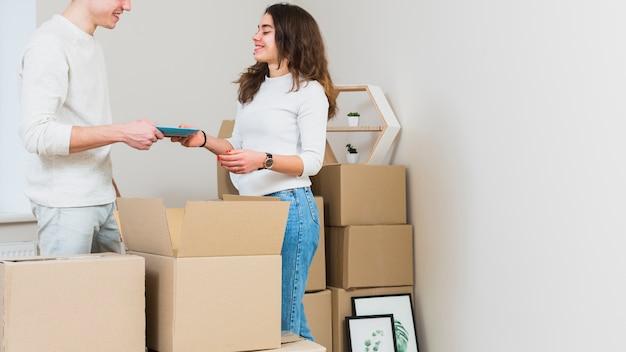 Portrait souriant d'un jeune couple déballant les cartons dans les nouveaux appartements
