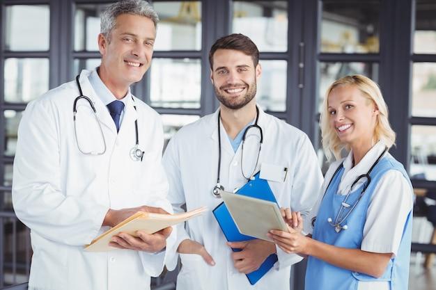 Portrait de souriant médecin senior avec des collègues