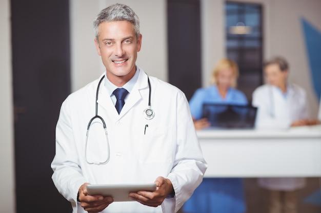 Portrait de souriant médecin senior tenant une tablette numérique