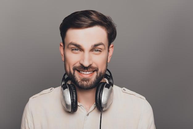 Portrait de souriant mélomane beau barbu avec un casque
