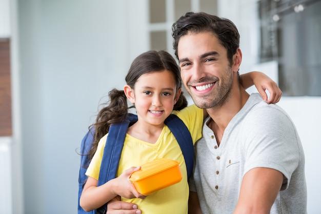 Portrait de souriant père et fille avec boîte à lunch