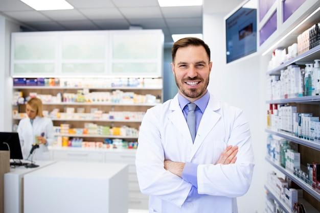 Portrait de souriant pharmacien caucasien debout en pharmacie avec les bras croisés.