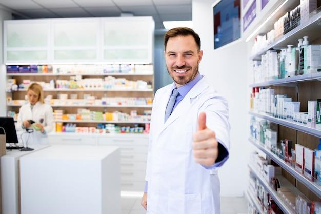 Portrait de souriant pharmacien caucasien debout en pharmacie avec les pouces vers le haut.