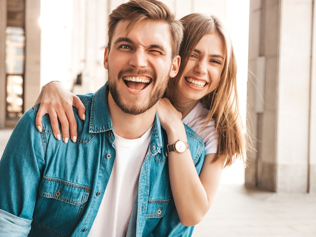 Portrait de souriante belle fille et son beau petit ami. femme en vêtements de jeans d'été décontracté. . un clin d'oeil