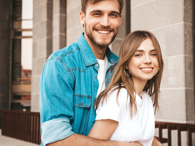 Portrait de souriante belle fille et son beau petit ami. femme en vêtements de jeans d'été décontracté. . étreindre