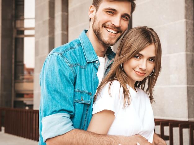 Portrait de souriante belle fille et son beau petit ami. femme en vêtements de jeans d'été décontracté. se regarder les uns les autres