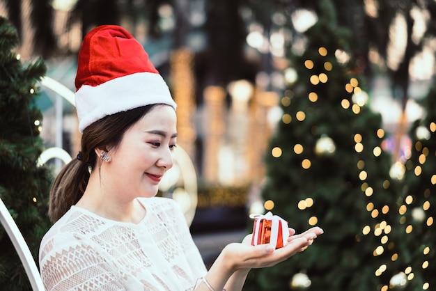 Portrait de souriante belle jeune femme asiatique avec un cadeau à la fête de noël