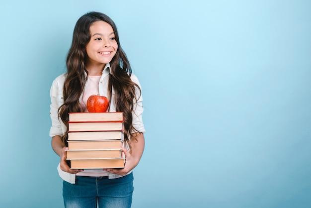Portrait de souriante jeune fille nerd tenant pile de livres avec apple à ce sujet. retour à l'école.