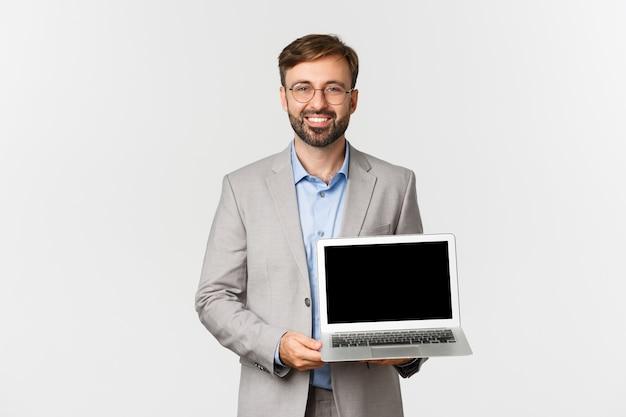 Portrait de sourire bel homme d'affaires et lunettes, démontrant l'écran d'ordinateur portable