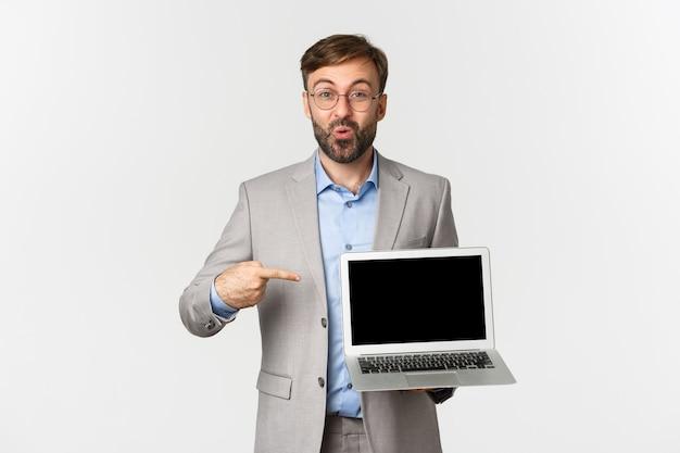 Portrait de sourire bel homme d'affaires et lunettes, pointant le doigt sur l'écran du portable