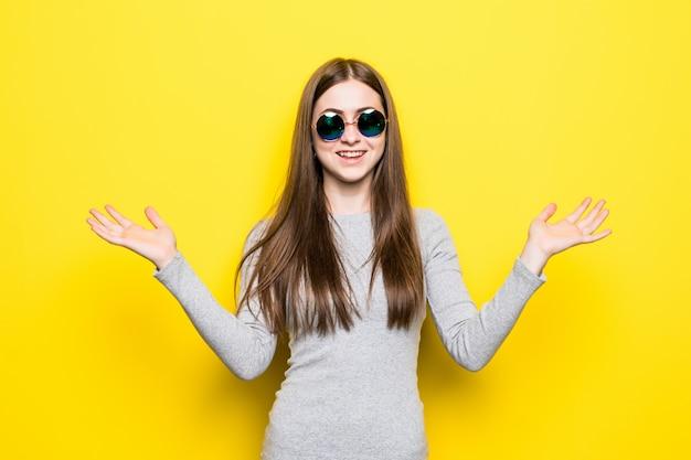 Portrait, de, sourire, belle femme, dans, lunettes soleil, et, robe, contre, de, mur jaune