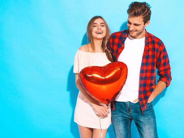 Portrait de sourire belle fille et son beau petit ami tenant des ballons en forme de coeur et rire. couple heureux en amour. joyeuse saint valentin. posant