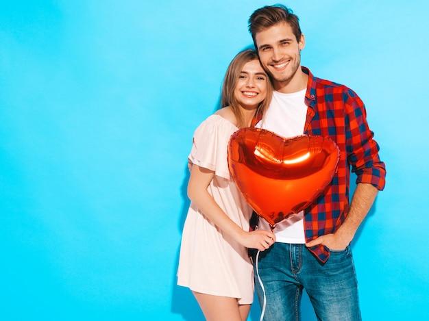 Portrait de sourire belle fille et son beau petit ami tenant des ballons en forme de coeur et rire. couple heureux en amour. joyeuse saint valentin