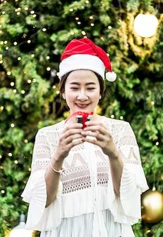 Portrait de sourire belle jeune femme asiatique avec un cadeau sur la foire de noël festive