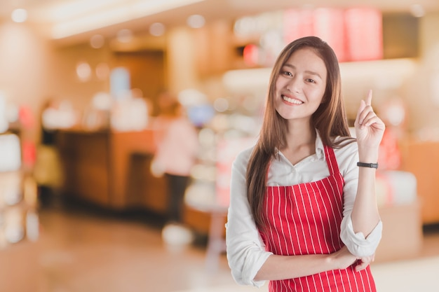 Portrait de sourire belle jeune femme asiatique porter tablier rouge