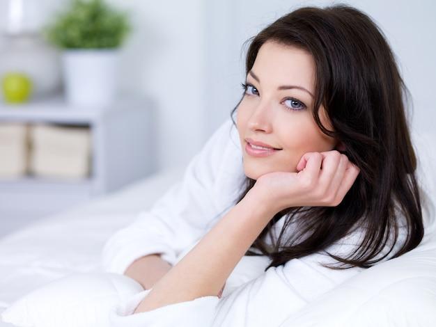 Portrait de sourire belle jeune femme brune à la maison
