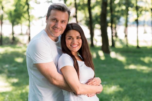 Portrait de sourire couple d'amoureux dans le parc