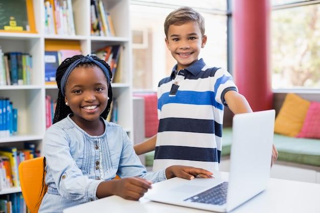 Portrait, de, sourire, écoliers, utilisation, a, ordinateur portable, dans, bibliothèque