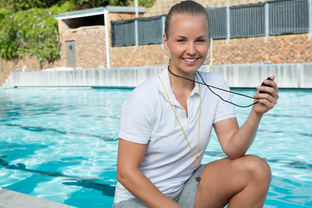 Portrait de sourire entraîneur de natation tenant un chronomètre près de la piscine