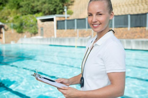 Portrait de sourire entraîneur de natation tenant le presse-papiers au bord de la piscine