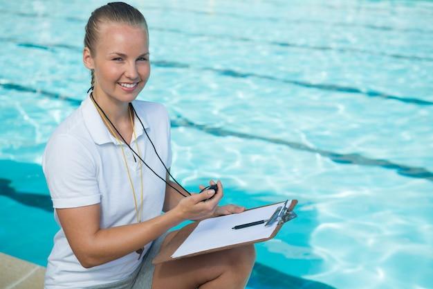 Portrait de sourire entraîneur de natation tenant le presse-papiers et chronomètre au bord de la piscine
