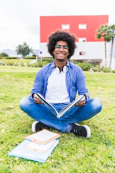 Portrait, de, sourire, étudiant africain africain, séance, sur, les, herbe verte, tenant livre, dans main