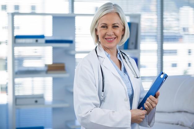 Portrait, sourire, femme, docteur, tenue, presse-papiers
