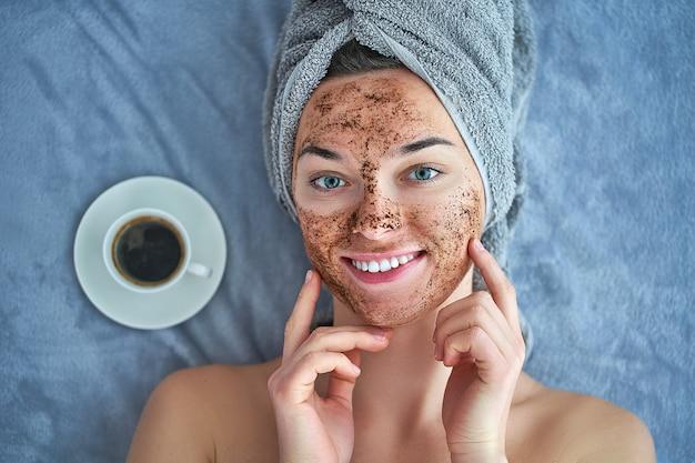Portrait, de, sourire, femme saine, dans, serviette bain, à, nettoyage naturel, figure, gommage café, pendant, journée spa