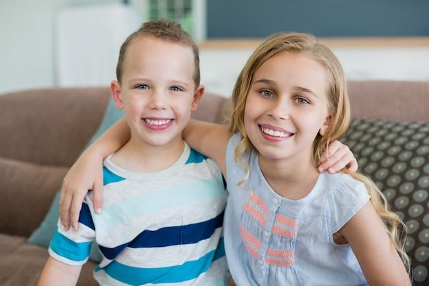 Portrait de sourire frère et soeur embrassant sur le canapé dans le salon à la maison