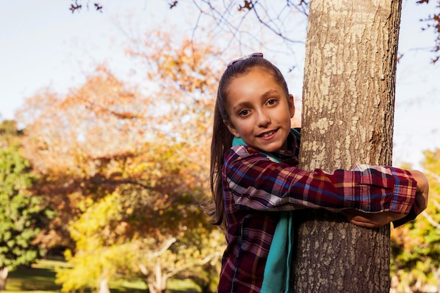 Portrait, de, sourire, girl, étreindre, arbre