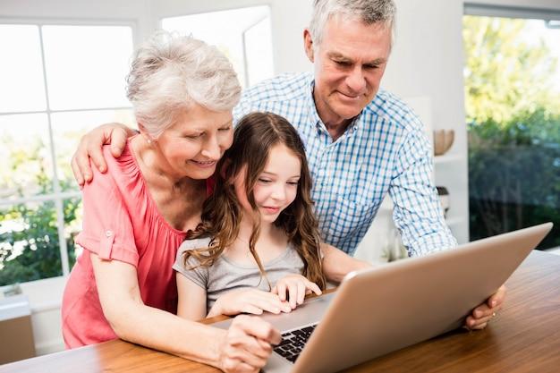 Portrait, sourire, grands-parents, petite-fille, ordinateur portable, chez soi