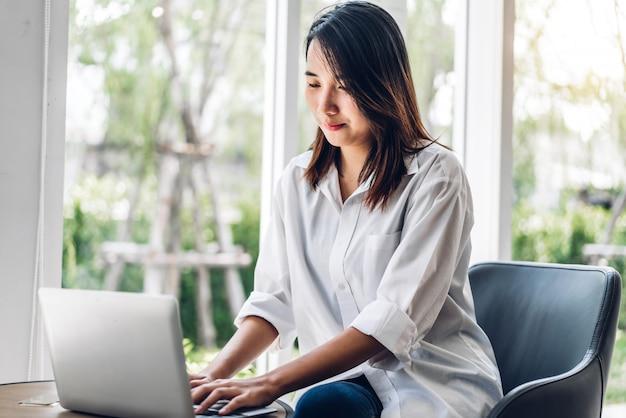 Portrait de sourire heureux belle femme asiatique se détendre à l'aide d'un ordinateur portable assis sur le canapé.