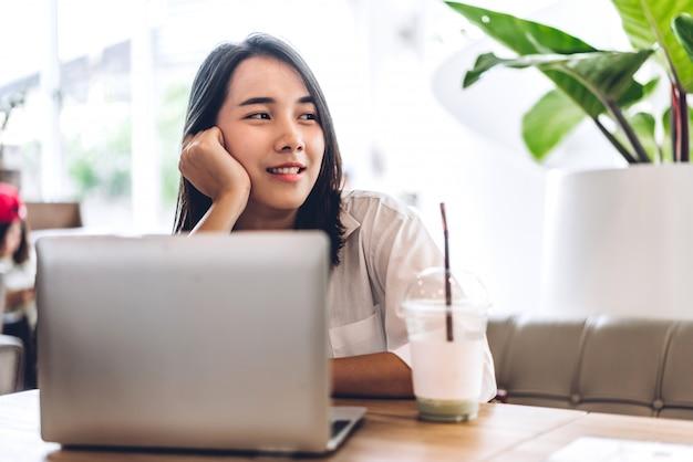 Portrait de sourire heureux belle femme asiatique se détendre à l'aide d'un ordinateur portable et à la recherche de quelque chose assis sur le canapé.