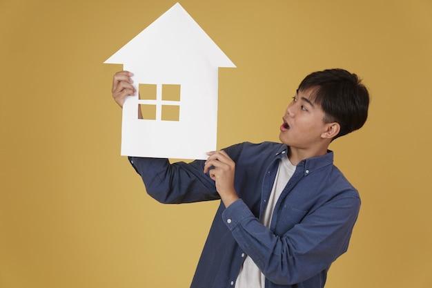 Portrait de sourire heureux joyeux jeune homme asiatique habillé avec désinvolture avec découpe de papier maison maison isolée. concept d'achat immobilier