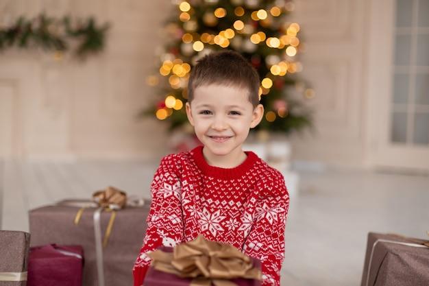 Portrait de sourire heureux petit garçon en pull tricoté rouge avec boîte de cadeau de noël près de l'arbre de noël. enfance heureuse. en attendant un conte de noël.