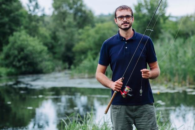 Portrait, de, sourire, homme, tenue, canne à pêche, près, les, lac