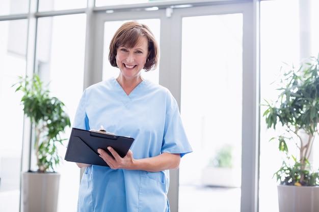 Portrait, de, sourire, infirmière, écriture, sur, presse-papiers